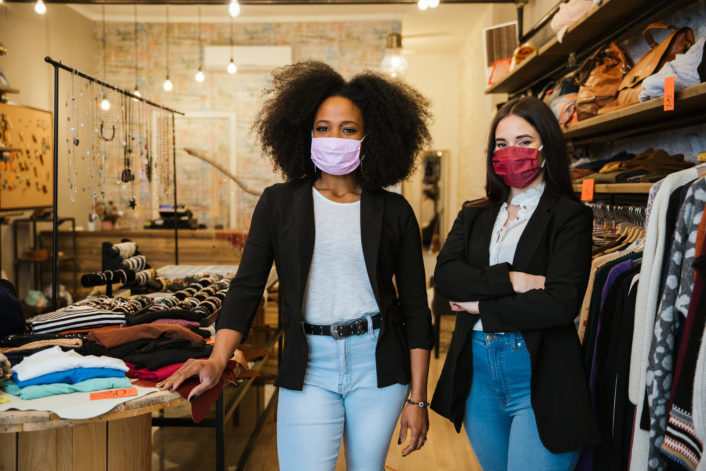 Portrait of two women owners of the clothes shop at the entrance to welcome customers during the Coronavirus Covid 19 pandemic wearing protective face masks – Millennial initiate a start up business